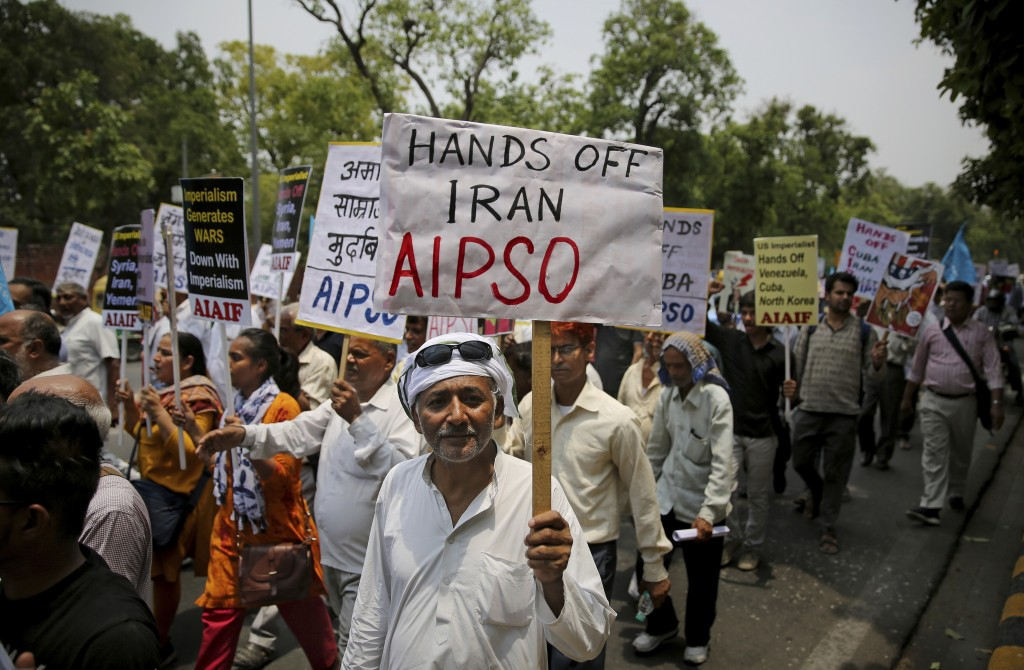 An activist of All India Peace and Solidarity Organization, AIPSO, a left-wing organization, holds a placard during a protest against the upcoming vis...