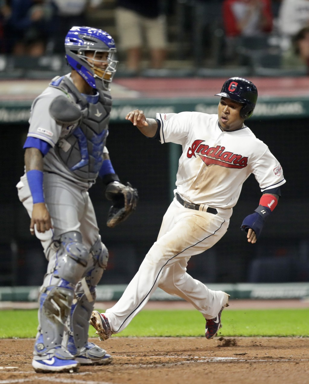 Cleveland Indians' Jose Ramirez, right, scores as Kansas City Royal catcher Martin Maldonado watches in the sixth inning in a baseball game, Monday, J...