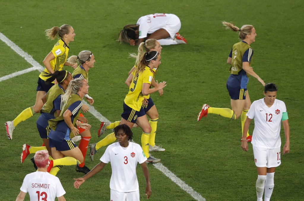 Sweden players run to their goalkeeper celebrating at the end of the Women's World Cup round of 16 soccer match between Sweden and Canada at the Parc ...