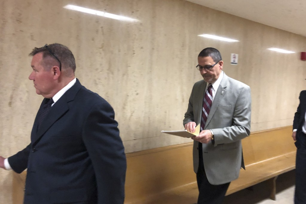 In this June 3, 2019 photo, Dr. Yasser Awaad, right, leaves court in Detroit. A jury has awarded more than $3 million to a woman who was misdiagnosed ...