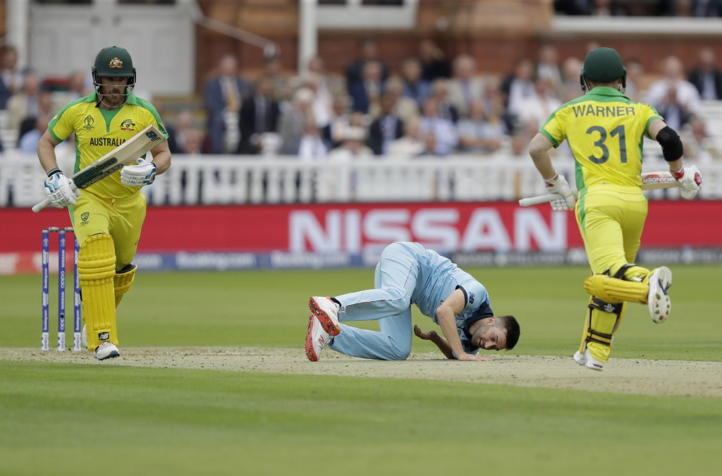 England's Mark Wood goes to ground after pitching a delivery as Australia's captain Aaron Finch, left, and Australia's David Warner add runs during th...