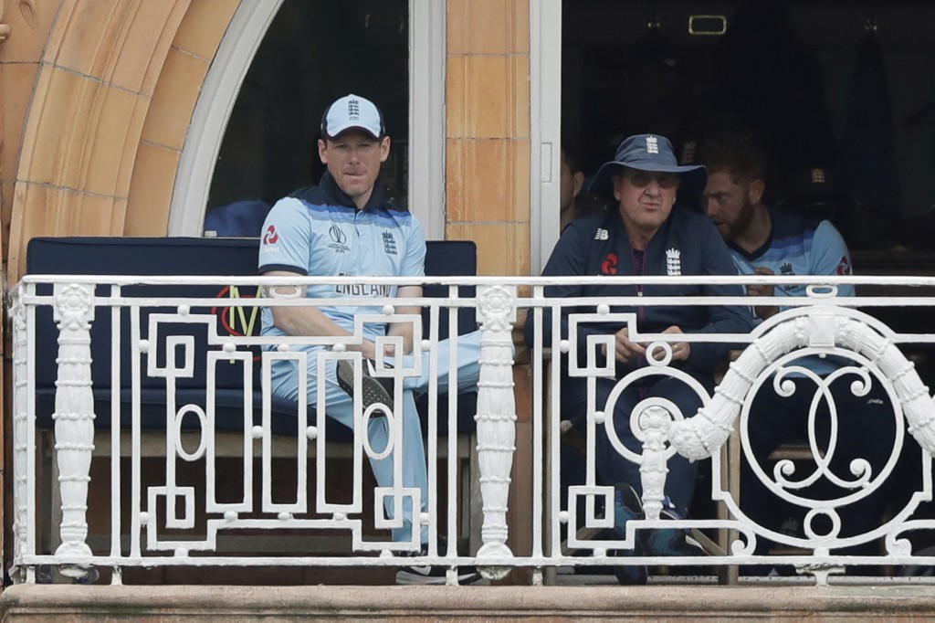 England captain Eoin Morgan, left, and England coach Trevor Bayliss sit on their team's balcony after Morgan was out for four runs during the Cricket ...