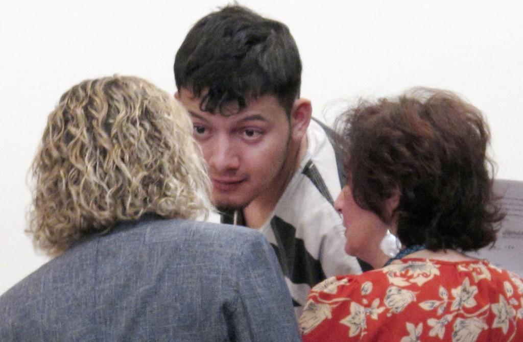 FILE - In this Jan. 24, 2019 file photo, Wilber Ernesto Martinez-Guzman, 19, of El Salvador, talks to his public defender and interpreter during his i...