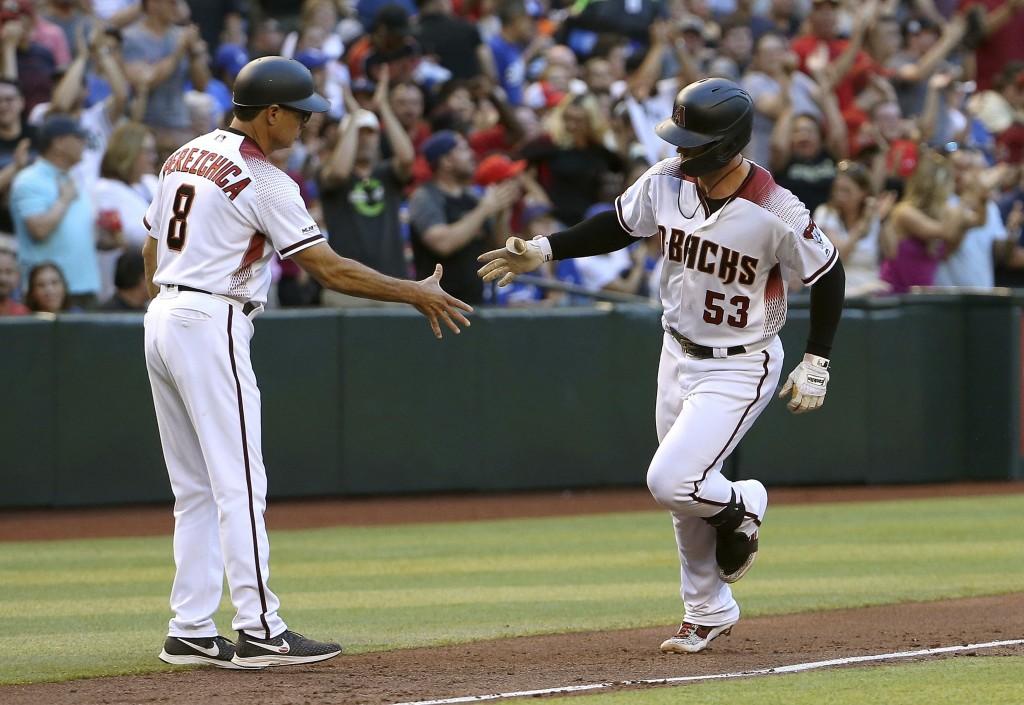 Arizona Diamondbacks' Christian Walker (53) shakes hands with third base coach Tony Perezchica (8) while rounding the bases after a three-run home run...