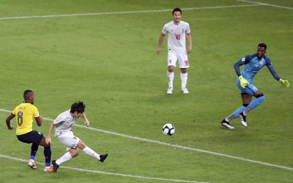 Japan's Shoya Nakajima, second left, strike the ball to score against Ecuador, as Ecuador's Carlos Gruezo, left, and goalkeeper Alexander Dominguez fa...