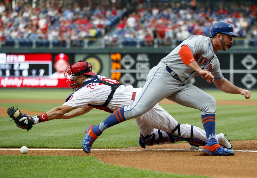 New York Mets' Pete Alonso, right, scores past Philadelphia Phillies catcher J.T. Realmuto on a double by Michael Conforto during the first inning of ...