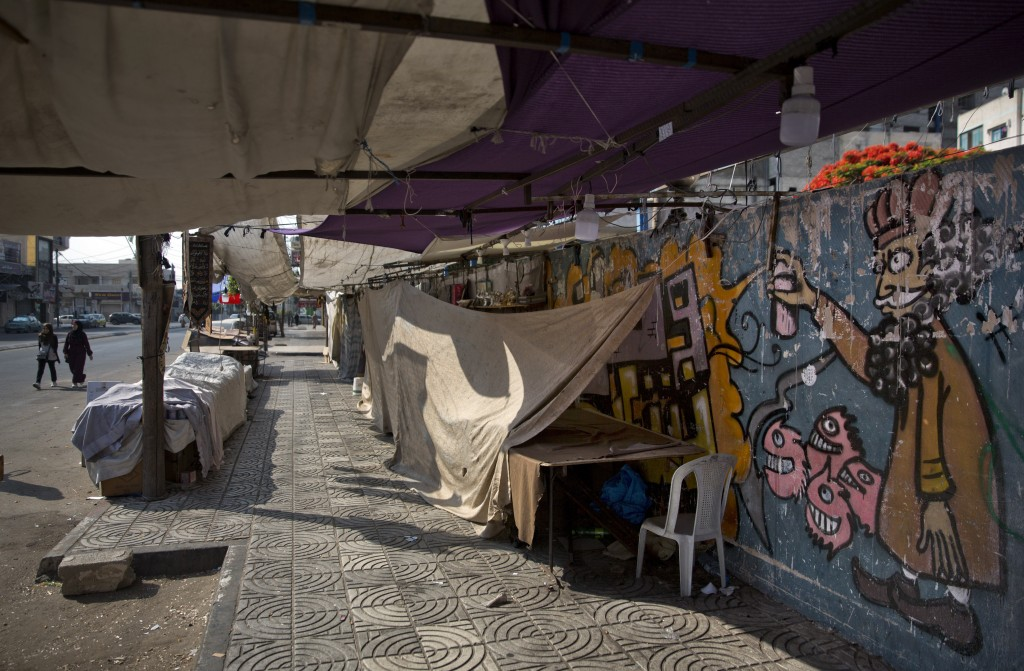 Palestinians walk next to covered vendors stalls in Gaza City, Tuesday, June 25, 2019, during a general strike against this week's economic conference...