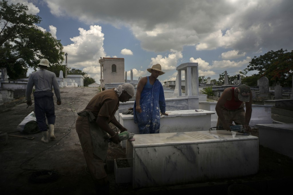 Workers polish a marble tomb at the Jewish cemetery in Guanabacoa, eastern Havana, Cuba, June 7, 2019. The restoration is the result of an initiative ...