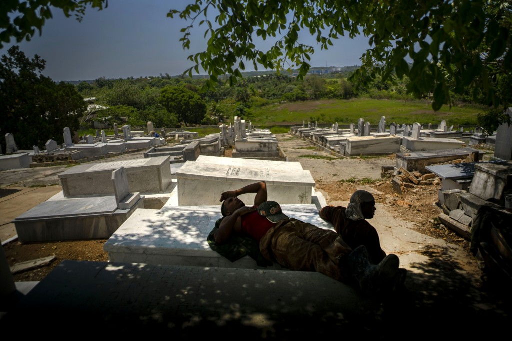 Workers repairing the Jewish cemetery take a break in the shade on top of tombs they already repaired in Guanabacoa, eastern Havana, Cuba, June 12, 20...