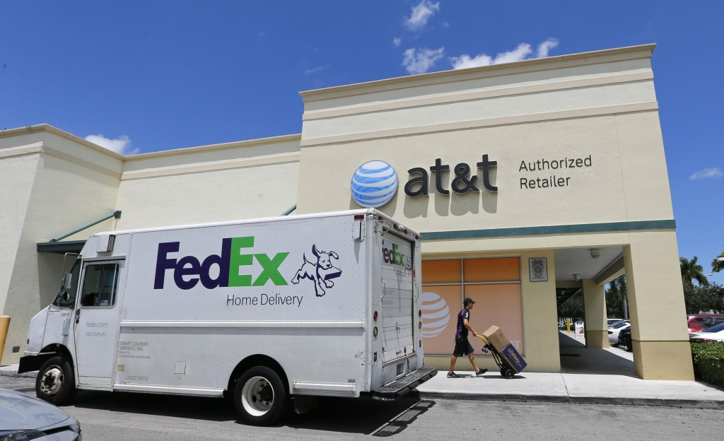 FILE - In this July 27, 2017, shows a Federal Express employee makes a delivery at an AT&T store in Hialeah, Fla. FedEx Corp. reports financial earnin...