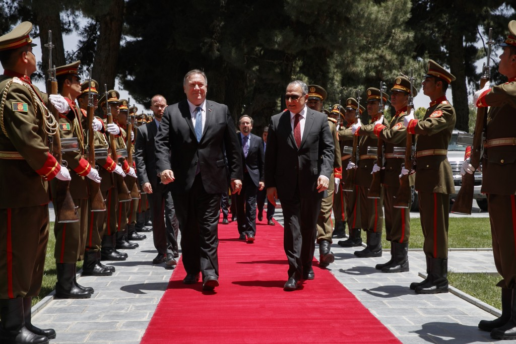 Secretary of State Mike Pompeo, center left, walks with Afghan President Ashraf Ghani's Chief of Staff Abdul Salam Rahimi, as he arrives at the Presid...