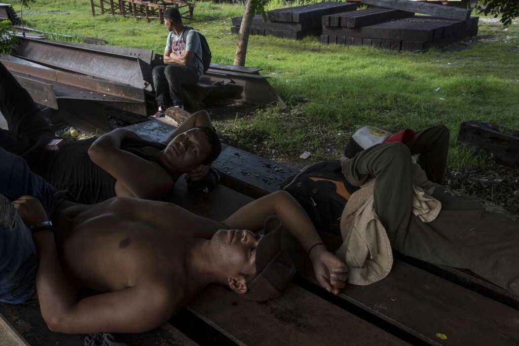 Central American migrants rest on discarded rail tracks as they wait for a train heading north, in Arriaga, Mexico, Monday, June 24, 2019. Mexican aut...