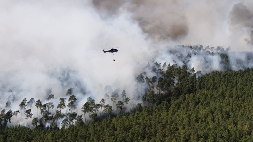 HANDOUT - A helicopter of the German Federal Police is fighting fire at a forest near Dahme-Spreewald, south of Berlin, Monday, June 24, 2019. Germany...