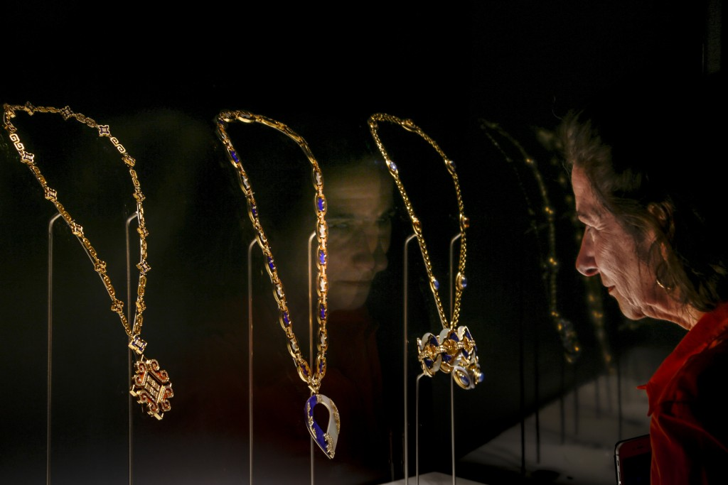 """A woman looks at necklaces on display during a preview of the exhibition """"Bulgari. The story, the dream"""" at St. Angel Castle in Rome, Tuesday, June 25..."""