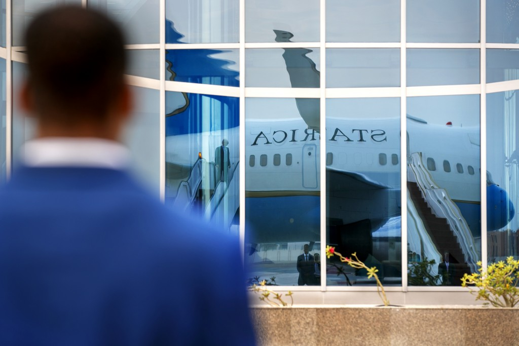 A member of Diplomatic Security stands guard on the tarmac as the plane for Secretary of State Mike Pompeo is reflected in a glass building, in prepar...