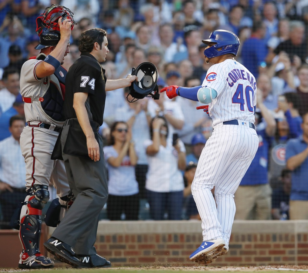 Chicago Cubs' Willson Contreras, right, yells at Atlanta Braves' Tyler Flowers, left, as he crosses the plate after hitting a home run as home plate u...