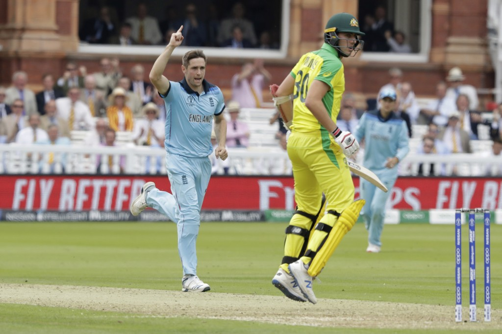 England's Chris Woakes celebrates taking the wicket of Australia's Pat Cummins during the Cricket World Cup match between England and Australia at Lor...