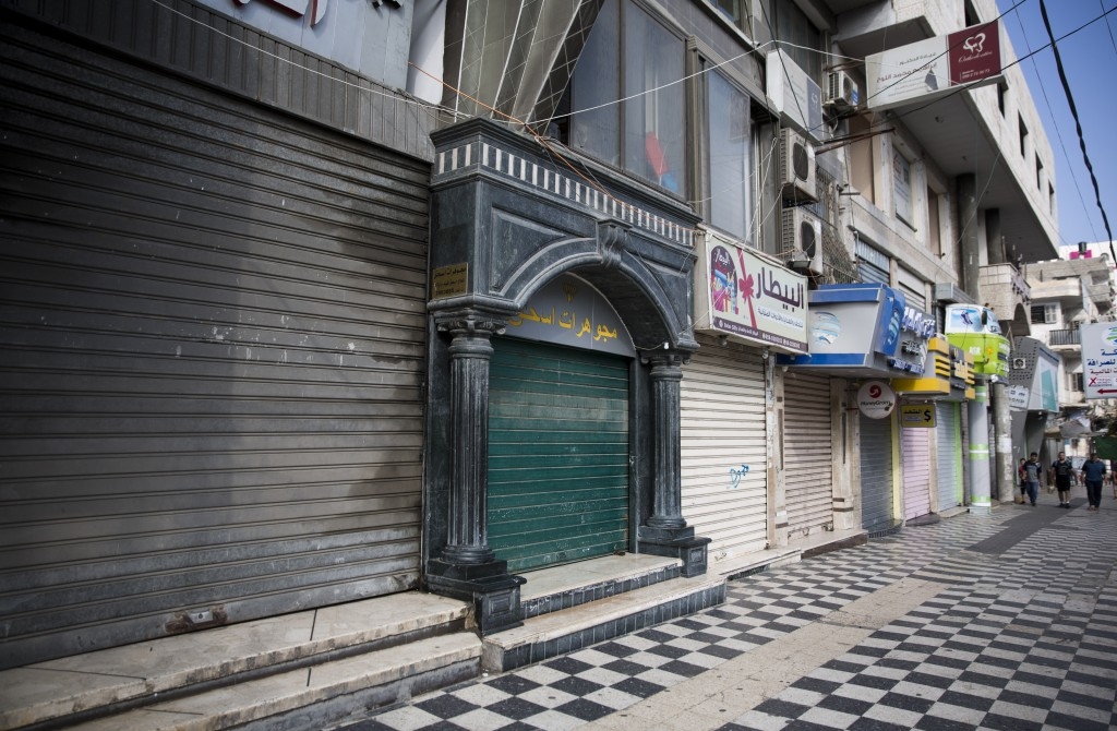 Palestinians walk next to closed shops in Gaza City, Tuesday, June 25, 2019, during a general strike against this week's economic conference in Bahrai...