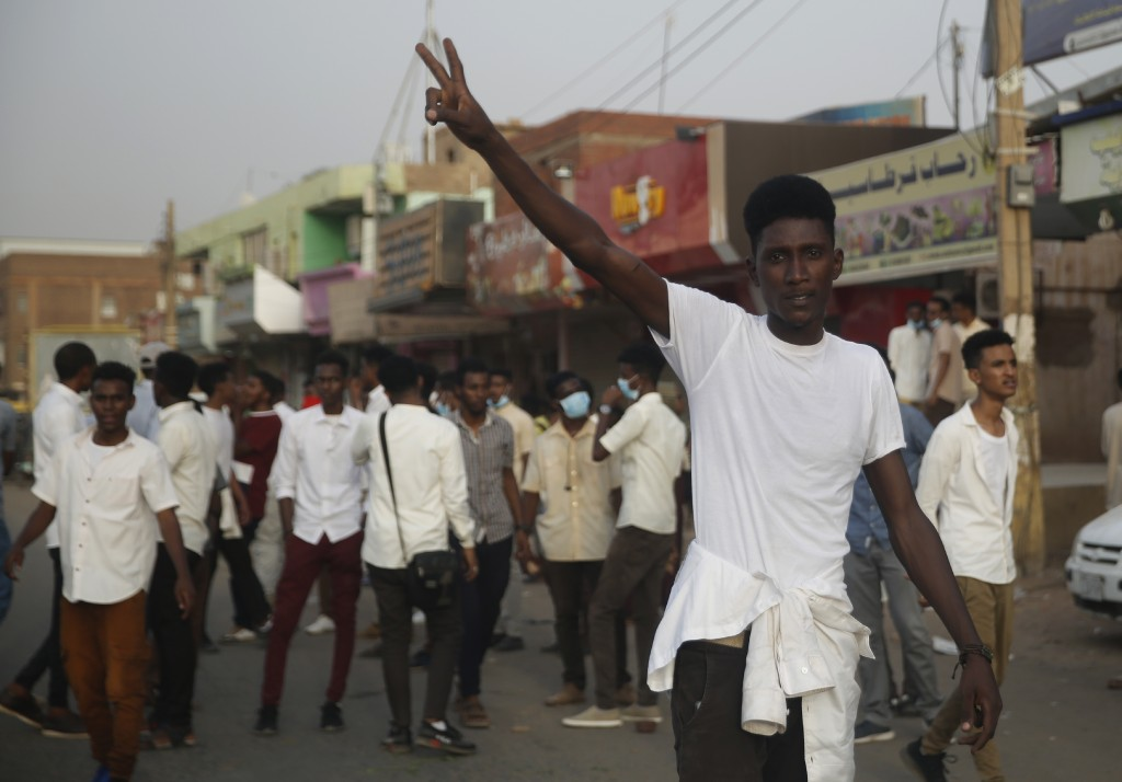 A protester flashes the victory sign, as others block a road during a protest, in Khartoum, Sudan, Monday, June 24, 2019. The United Nations' top huma...