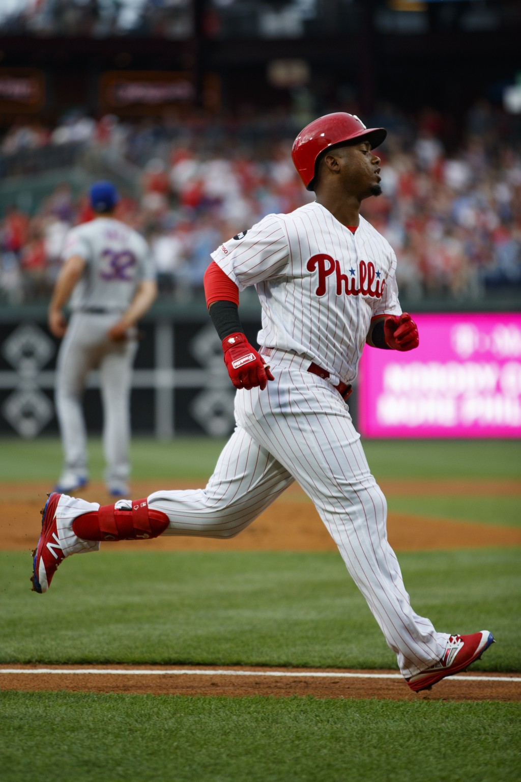 Philadelphia Phillies' Jean Segura, foreground, rounds the bases after hitting a home run off New York Mets starting pitcher Steven Matz, back left, d...