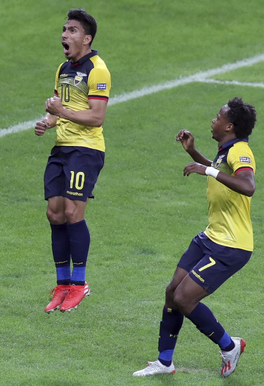 Ecuador's Angel Mena, left, celebrates scoring his team's equalizer against Japan, as teammate Romario Ibarra runs next to him during a Copa America G...
