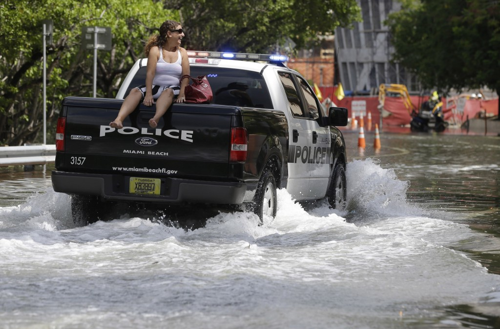 FILE- In this Sept. 30, 2015 file photo, a woman gets a ride on a police truck navigating a flooded street in Miami Beach, Fla. The street flooding wa...