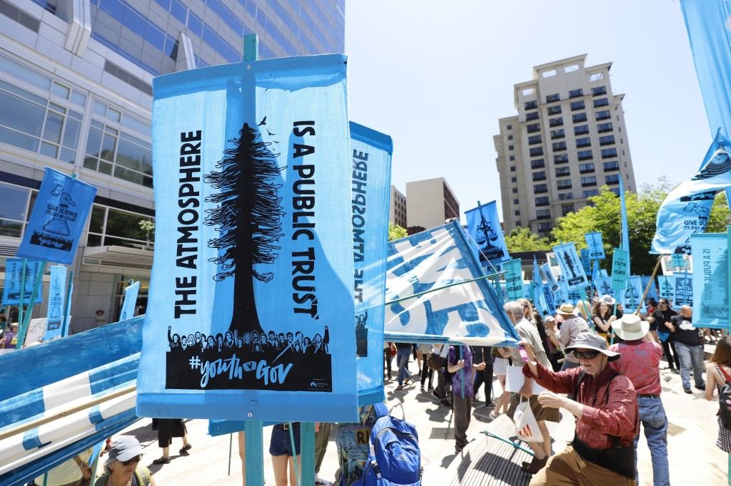 FILE - In this June 4, 2019, file photo, supporters attend a rally for a group of young people who filed a lawsuit saying U.S. energy policies are cau...