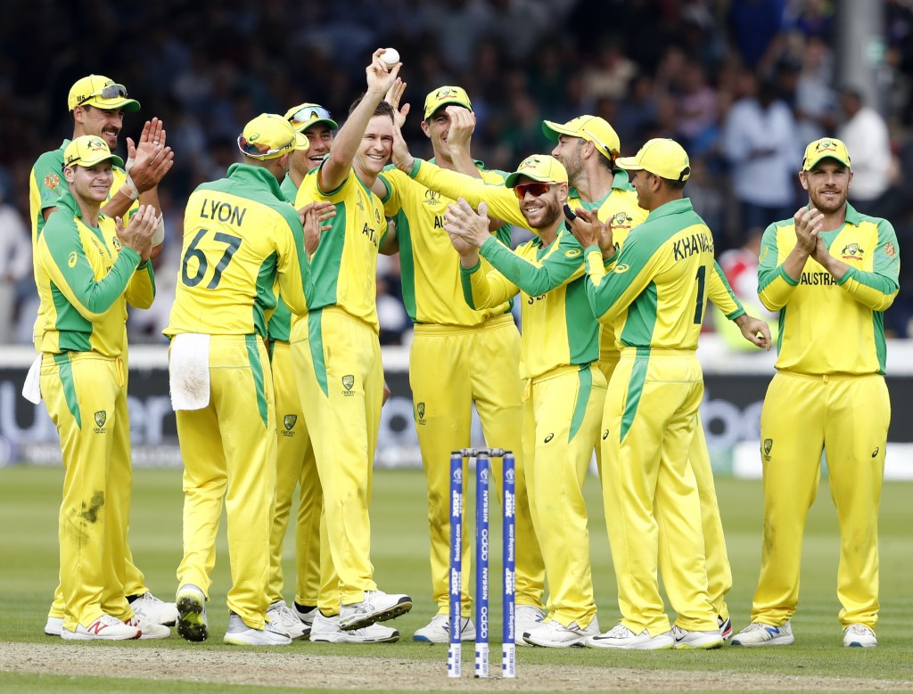 Australia's Jason Behrendorff, centre, holds up the ball as he celebrates with teammates after taking the wicket of England's Jofra Archer during the ...