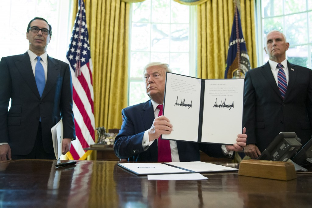 FILE - In this Monday, June 24, 2019 file photo, President Donald Trump holds up a signed executive order to increase sanctions on Iran, accompanied b...