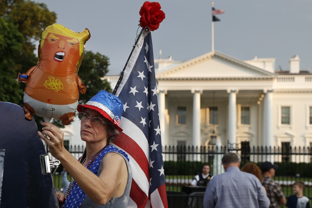 """FILE - In this May 18, 2019 file photo, a woman who described herself only as """"a resister"""" adjusts a """"Trump baby"""" balloon at the start of a protest ag..."""