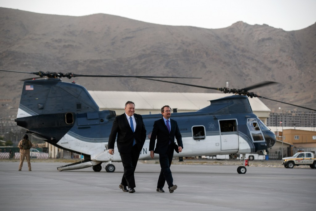 Secretary of State Mike Pompeo, left, walks from a helicopter with U.S. Ambassador to Afghanistan John Bass, Tuesday, June 25, 2019, as Pompeo returns...