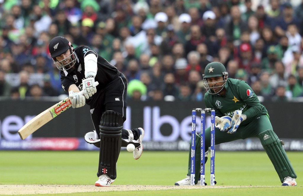 New Zealand's captain Kane Williamson, left, plays a shot as Pakistan's captain Sarfaraz Ahmed watches on during the Cricket World Cup match between N...