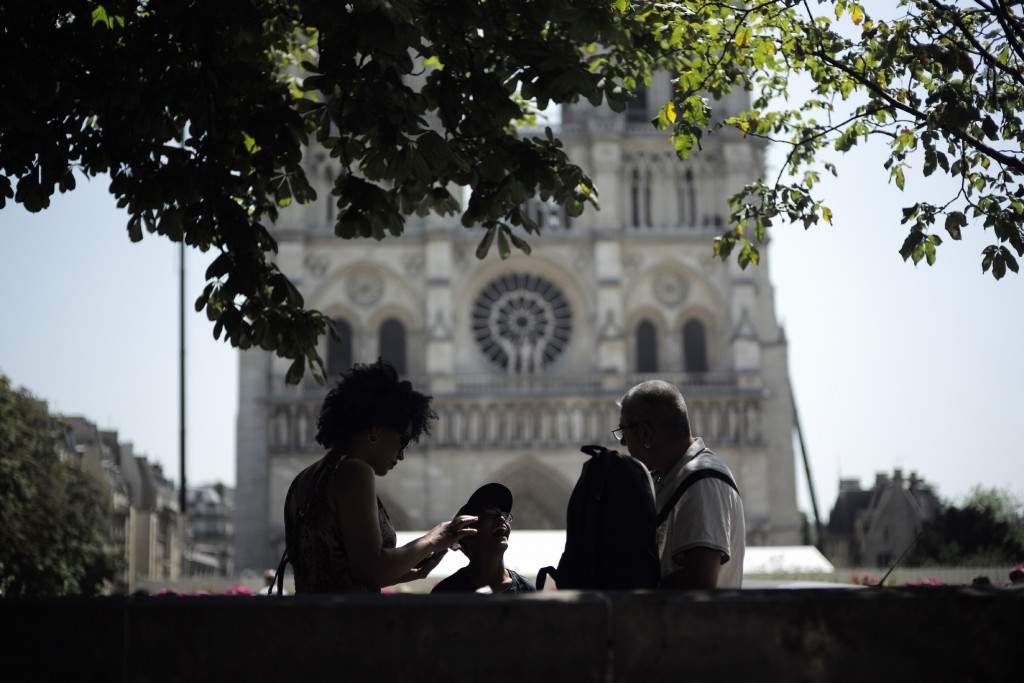 Tourists chat under a tree in front of Notre Dame Cathedral, Wednesday, June 26, 2019 in Paris. High temperatures are expected to go up to 39 degrees