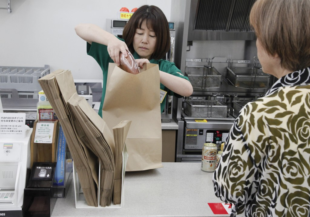In this June 17, 2019, photo, a salesclerk puts goods into a paper bag after a customer purchased them, at a Seven-Eleven store in Yokohama, near Toky