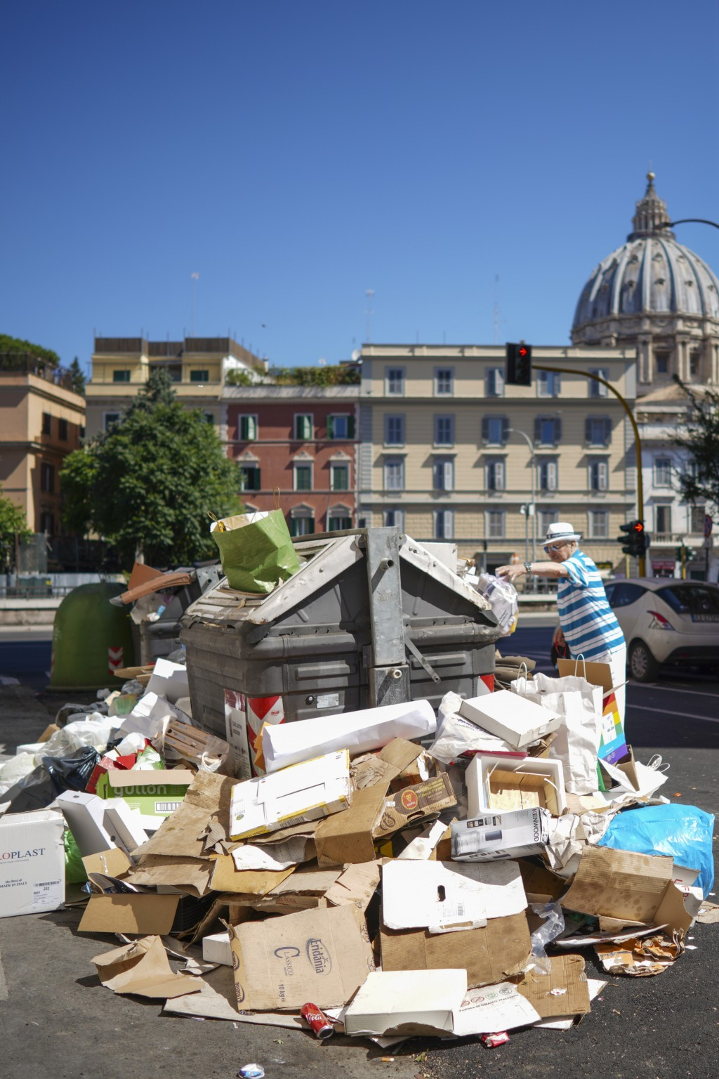 In this photo taken on Monday, June 24, 2019, a man stands by uncollected garbage in Rome. Doctors in Rome are warning of possible health hazards caus...