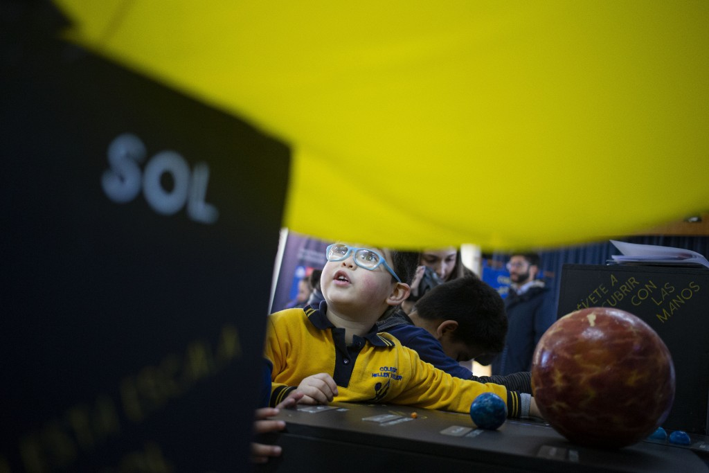 Blind school children take part in a sensorial experience with tools created by NASA and Edinburgh University to experience an eclipse, during an even...