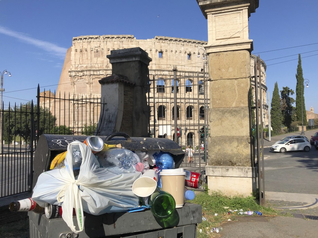 In this photo taken on Tuesday, June 25, 2019, a man walks past a pile of garbage as St. Peter's Dome is visible in background, in Rome. Doctors in Ro...