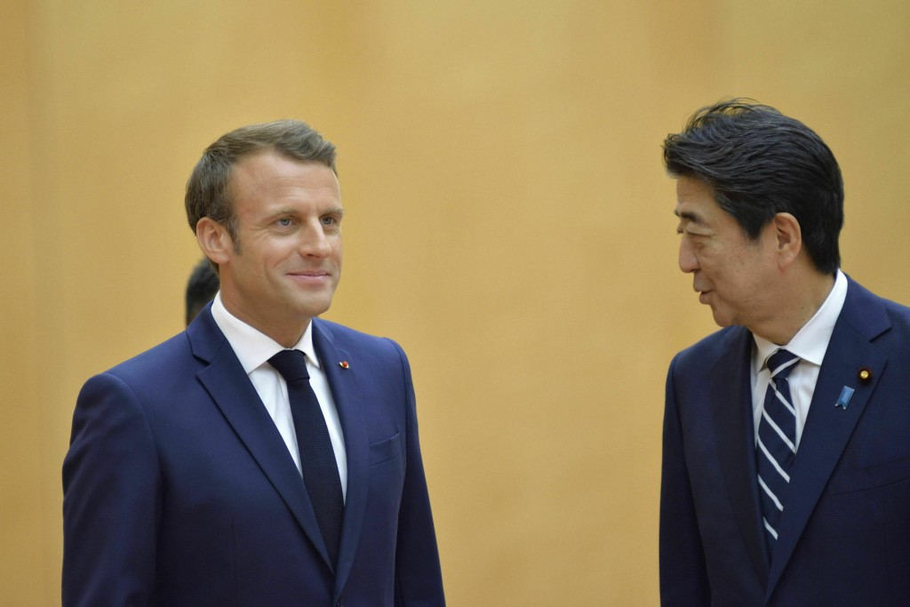 French President Emmanuel Macron, left, meets with Japanese Prime Minister Shinzo Abe prior to their meeting at Abe's official residence, Wednesday, J...