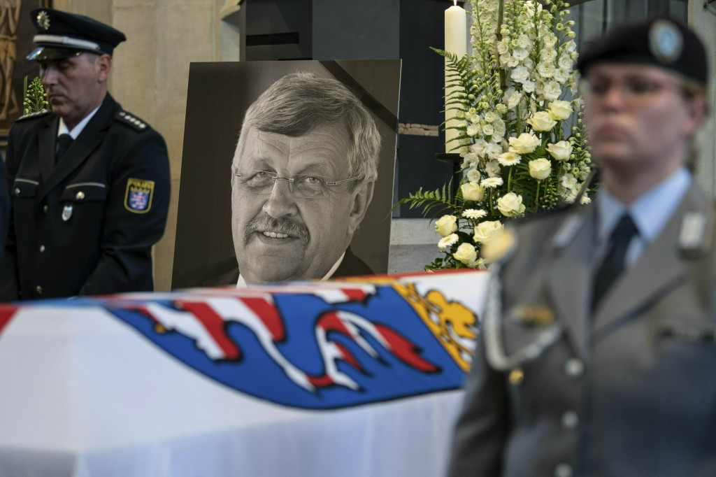 FILE-In this June 13, 2019 file photo a picture of Walter Luebcke stands behind his coffin during the funeral service in Kassel, Germany. Germany's to...