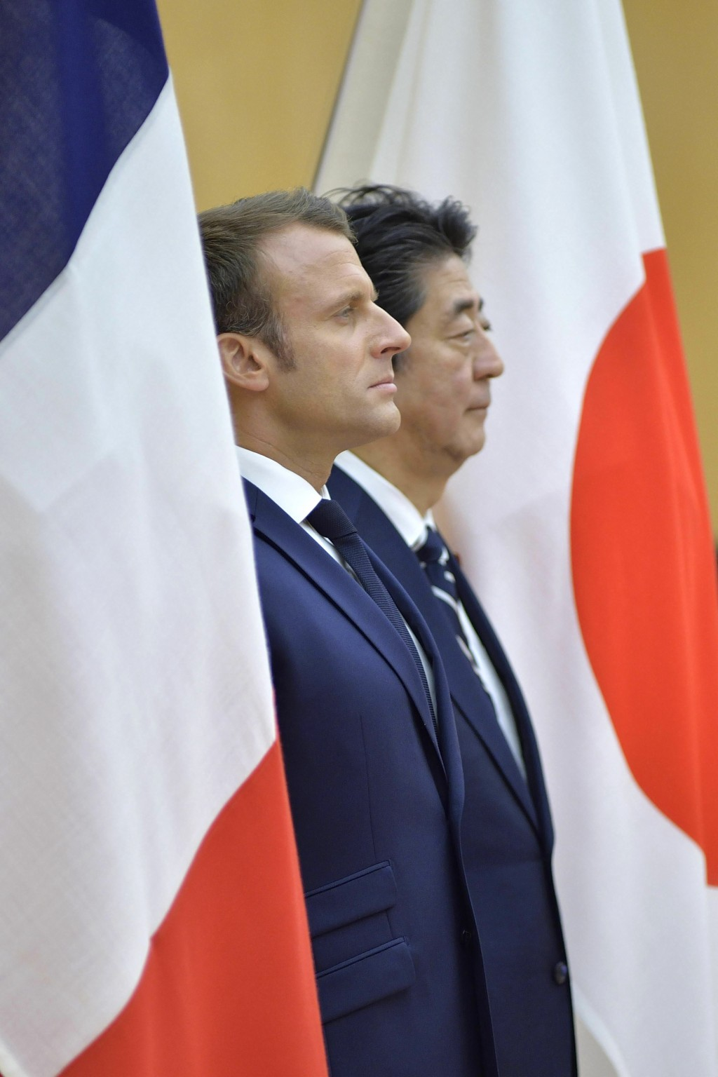 French President Emmanuel Macron, left, and Japanese Prime Minister Shinzo Abe review and honor guard prior to their meeting at Abe's official residen...