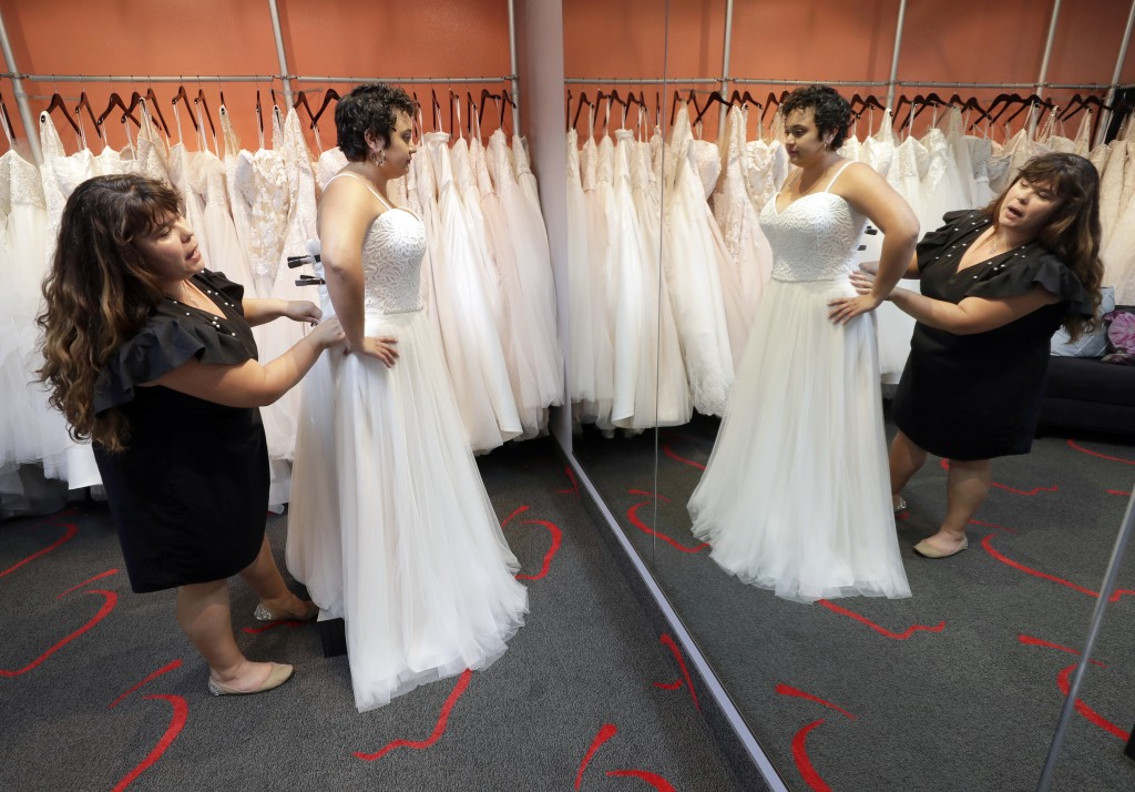 In this Friday, June 21, 2019, photo Ann Campeau, left, owner of Strut Bridal, fits a new dress on inventory manager Stefanie Zuniga at her shop in Te...
