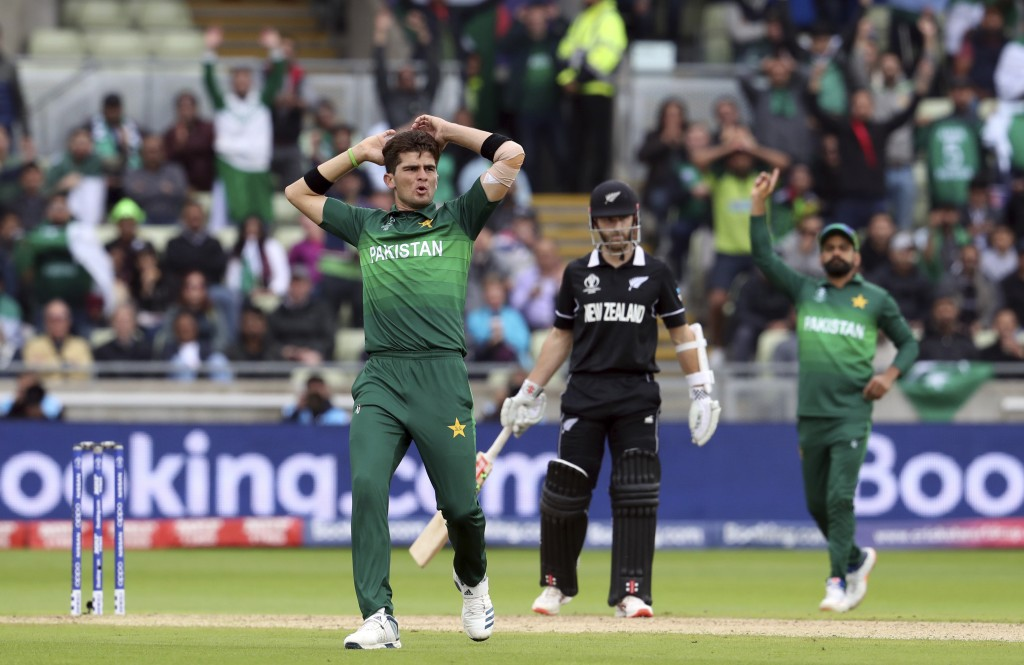 Pakistan's bowler Shaheen Afridi, left, reacts after his delivery against New Zealand's batsman James Neesham during the Cricket World Cup match betwe...