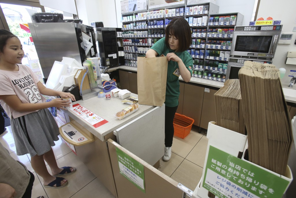 In this June 17, 2019, photo, a salesclerk puts goods into a paper bag after a customer purchased them, at a Seven-Eleven store in Yokohama, near Toky...