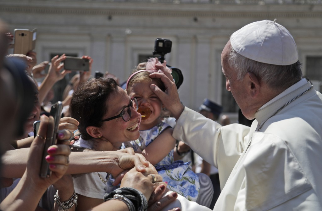 Pope Francis blesses a child during his weekly general audience in St. Peter's Square, at the Vatican, Wednesday, June 26, 2019. (AP Photo/Gregorio Bo...