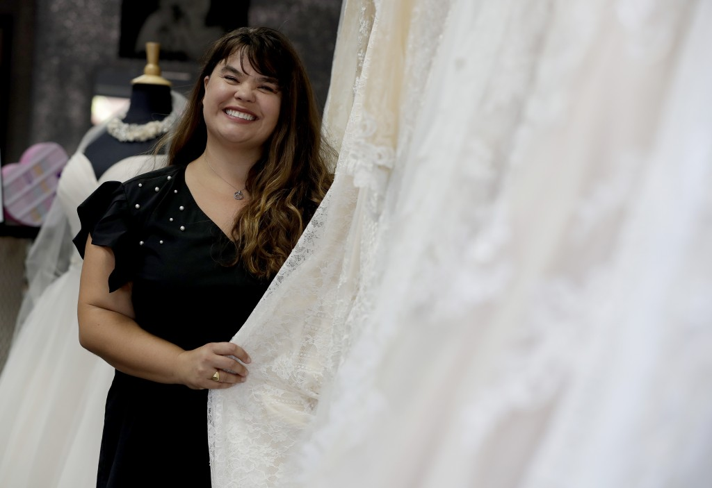 In this Friday, June 21, 2019, photo Ann Campeau, owner of Strut Bridal, stands in her shop in Tempe, Ariz. Cut-rate prices on websites that sell wedd...