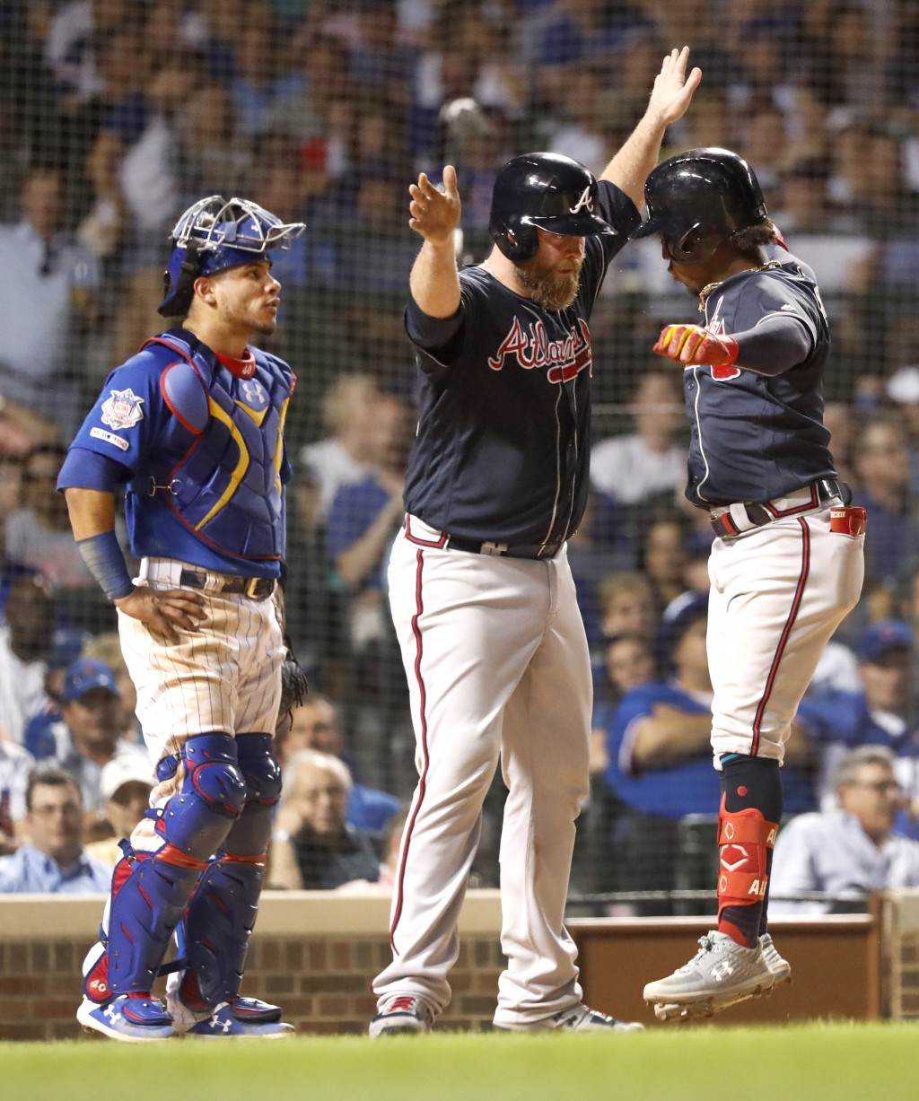 Atlanta Braves' Brian McCann, center, greets Ozzie Albies, right, at home after the pair scored on Albies' two-run home run as Chicago Cubs catcher Wi...