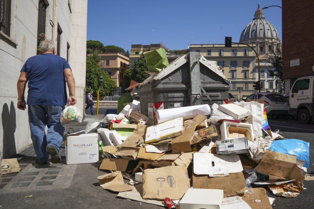 In this photo taken on Monday, June 24, 2019, a man walks past a pile of garbage as St. Peter's Dome is visible in background, in Rome. Doctors in Rom...
