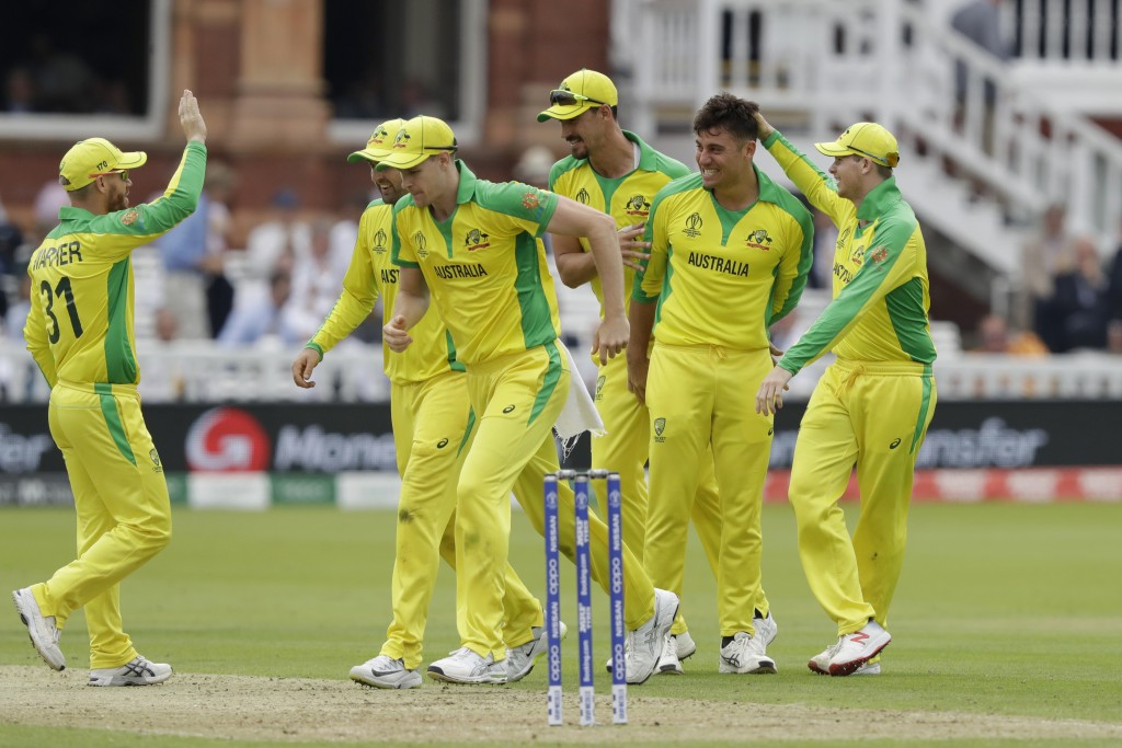 Australia's Marcus Stoinis, second right, celebrates taking the wicket of England's Jos Buttler during the Cricket World Cup match between England and...