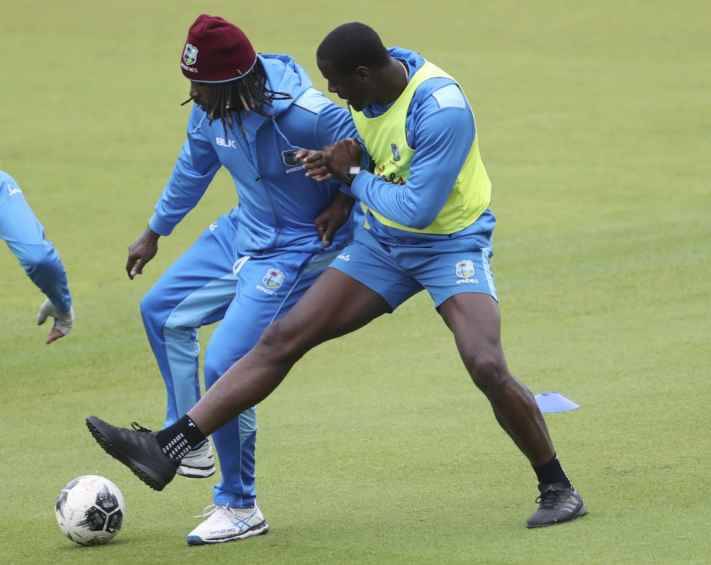 West Indies' Chris Gayle, left, and Carlos Brathwaite vie for the ball during a friendly game of soccer at a training session ahead of their Cricket W...