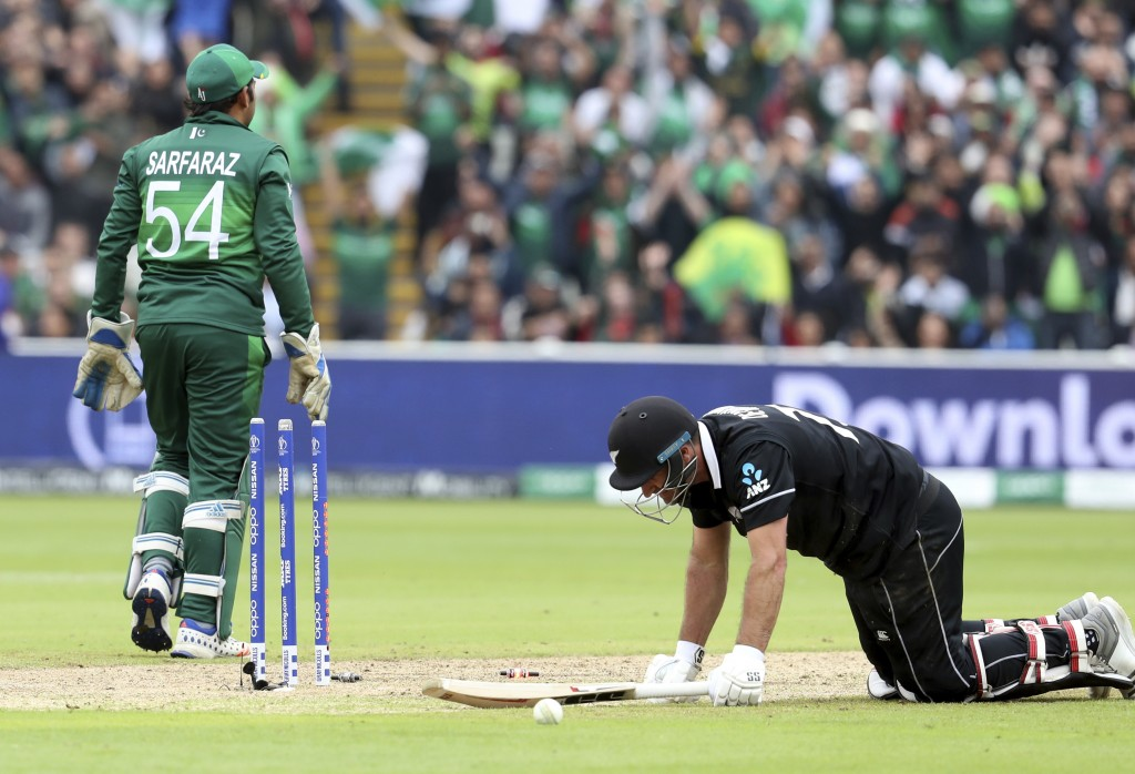 New Zealand's batsman Colin de Grandhomme, right, is run out as Pakistan's captain Sarfaraz Ahmed walks away during the Cricket World Cup match betwee...